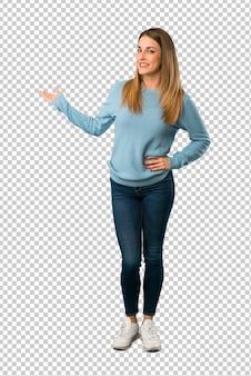 Mujer rubia con camisa azul apuntando hacia atrás y presentando un producto.