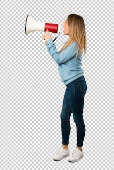 Mujer rubia con camisa azul gritando a través de un megáfono para anunciar algo en posición lateral