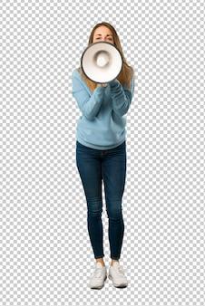 Mujer rubia con camisa azul gritando a través de un megáfono para anunciar algo