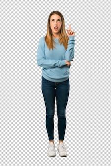 Mujer rubia con camisa azul pensando una idea apuntando el dedo hacia arriba