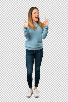 Mujer rubia con la camisa azul que muestra la muestra aceptable con y que da un pulgar encima del gesto