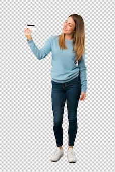 Mujer rubia con camisa azul sosteniendo una tarjeta de crédito y pensando