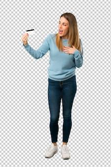 Mujer rubia con camisa azul sosteniendo una tarjeta de crédito y sorprendida
