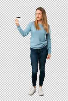 Mujer rubia con camisa azul tomando una tarjeta de crédito sin dinero