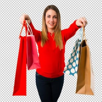 Mujer rubia joven feliz con el bolso de compras