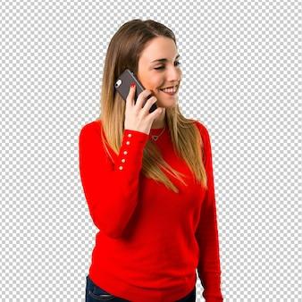 Mujer rubia joven feliz que habla con el móvil
