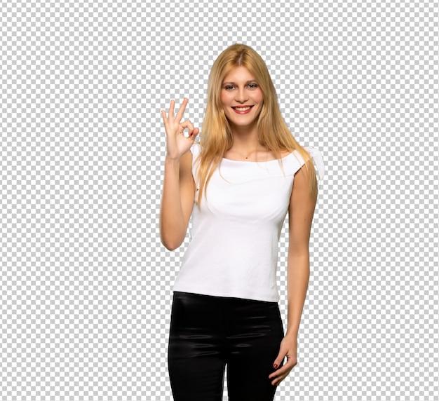 Mujer rubia joven que muestra una muestra aceptable con los dedos