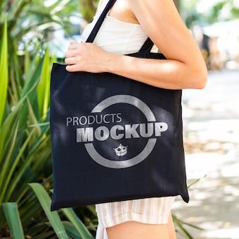 Mujer rubia de lado sosteniendo una maqueta de bolsa negra