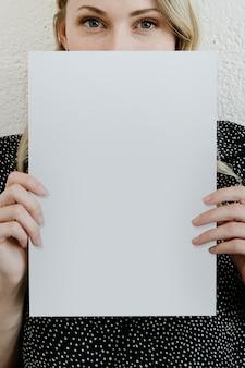 Mujer rubia mostrando una maqueta de cartel blanco en blanco