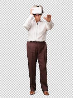 Mujer senior de cuerpo completo emocionada y entretenida, jugando con gafas de realidad virtual, explorando un mundo de fantasía, tratando de tocar algo