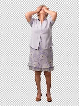 Mujer senior de cuerpo completo frustrada y desesperada, enojada y triste con las manos en la cabeza