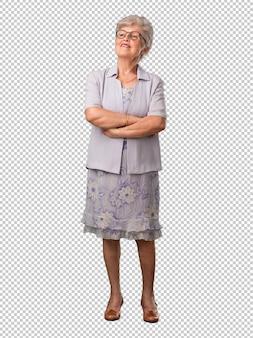Mujer senior de cuerpo completo mirando hacia arriba, pensando en algo divertido y teniendo una idea, concepto de imaginación, feliz y emocionada