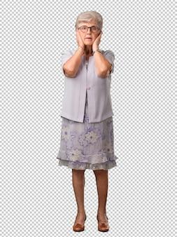 Mujer senior de cuerpo completo que cubre las orejas con las manos, enojada y cansada de escuchar un sonido