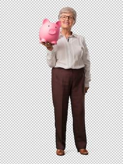 Mujer senior de cuerpo completo segura y alegre sosteniendo una alcancía