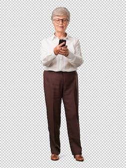 Mujer senior de todo el cuerpo, feliz y relajada, tocando el móvil, utilizando internet y redes sociales, sentimiento positivo del futuro y modernidad.