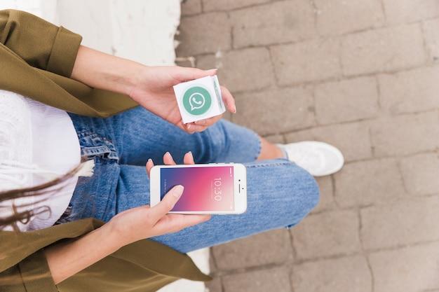 Mujer con smartphone y cubo de whatsapp