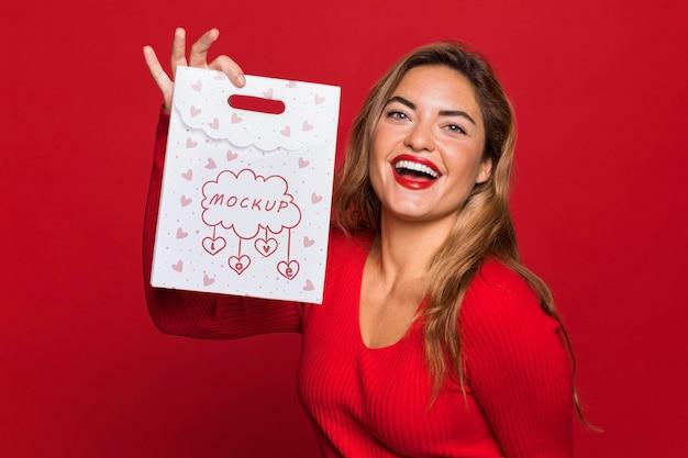 Mujer sonriente sosteniendo bolsa de tiro medio