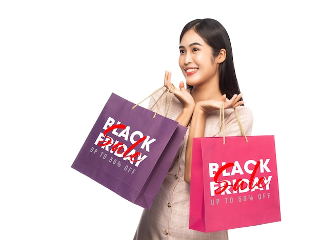 Mujer sonriente sosteniendo bolsas de compras con maqueta de campaña de viernes negro