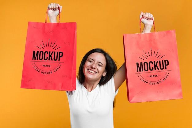 Mujer sonriente sosteniendo maqueta de bolsas de compras