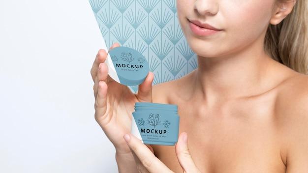 Mujer sonriente sosteniendo una maqueta de productos para el cuidado de la piel