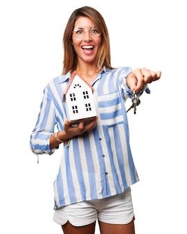 Mujer sonriente sujetando llaves y una casa de juguetes