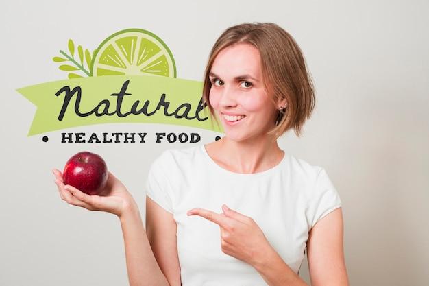 Mujer sonriente sujetando una manzana