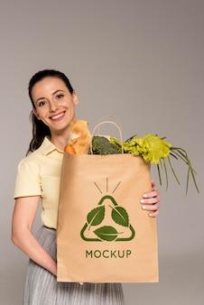 Mujer sosteniendo una bolsa de tiro medio con verduras