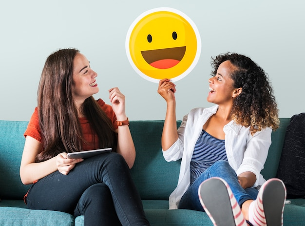 Mujer sosteniendo emoticones en un sofá