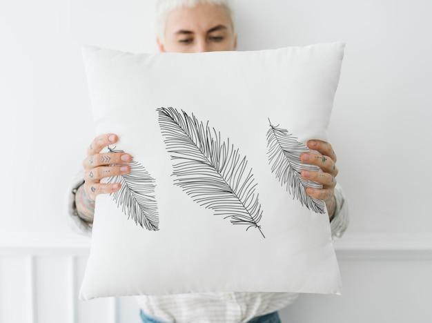 Mujer sosteniendo una maqueta de almohada blanca frondosa