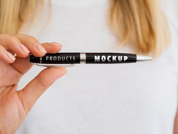 Mujer sosteniendo una maqueta de bolígrafo negro