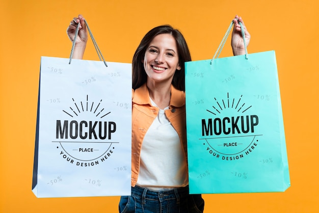 Mujer sosteniendo maqueta de bolsas de compras
