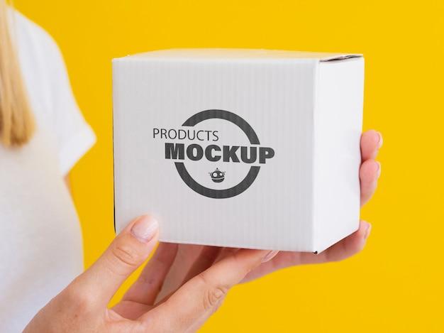 Mujer sosteniendo una maqueta de caja blanca