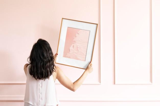 Mujer sosteniendo maqueta de marco de imagen