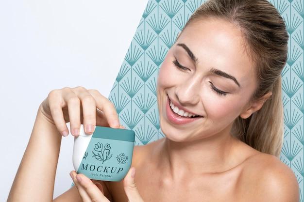 Mujer sosteniendo una maqueta de productos para el cuidado de la piel