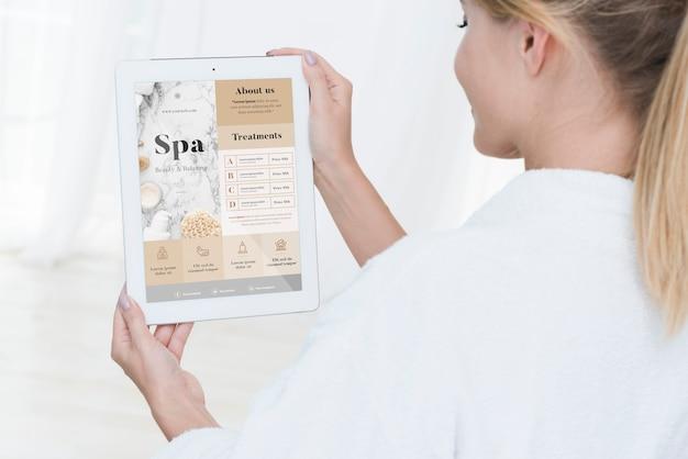 Mujer sosteniendo maqueta de tableta con ofertas de spa