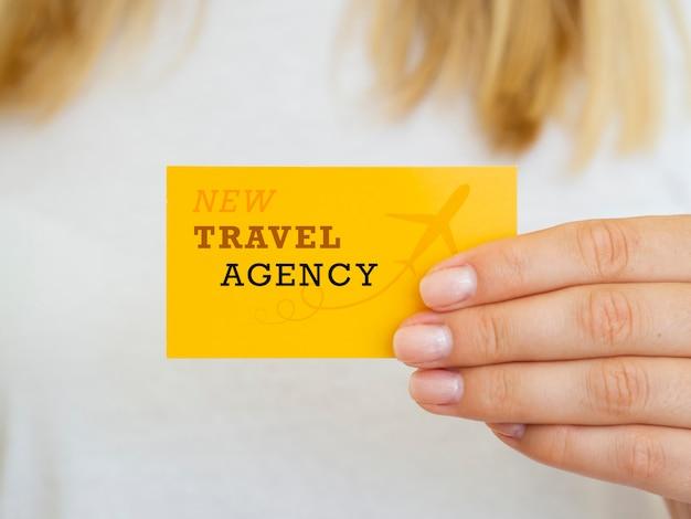 Mujer sosteniendo una maqueta de tarjeta de agencia de viajes
