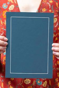 Mujer sosteniendo una maqueta de tarjeta enmarcada azul