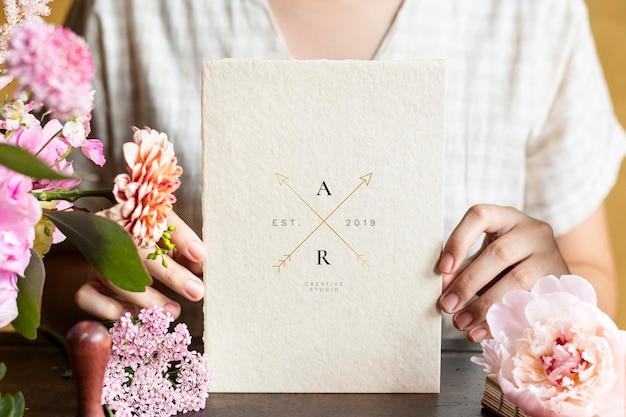 Mujer sosteniendo una maqueta de tarjeta rodeada de flores