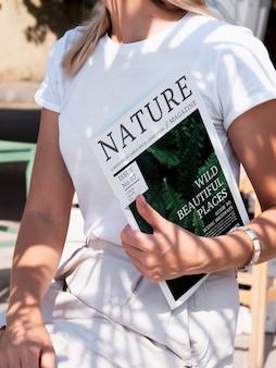 Mujer sosteniendo una revista de naturaleza simulacro