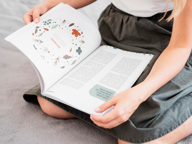 Mujer sosteniendo una revista sobre sus rodillas simulacro