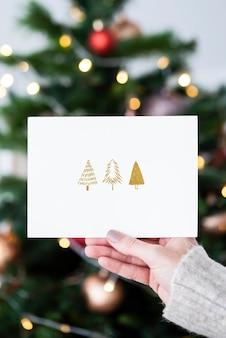 Mujer sosteniendo una tarjeta de navidad frente a una maqueta de árbol de navidad