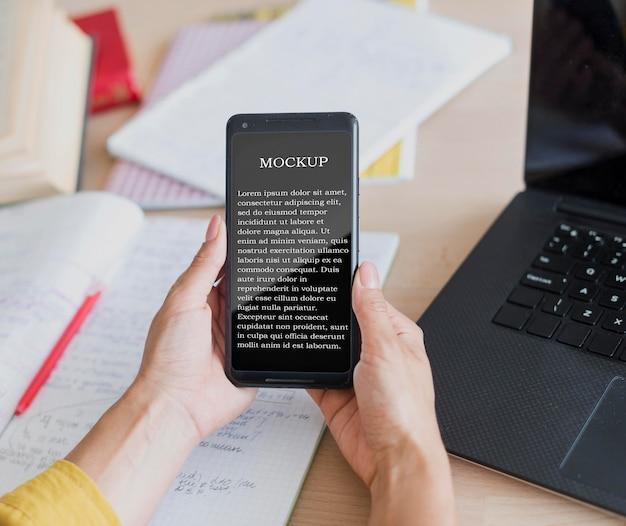 Mujer sosteniendo un teléfono móvil de maqueta