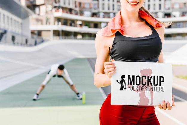 Mujer sosteniendo vista frontal de maqueta de fitness