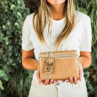 Mujer sujetando maqueta de caja de regalo