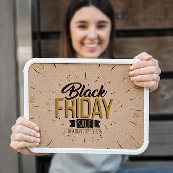 Mujer sujetando mockup de marco con concepto de black friday