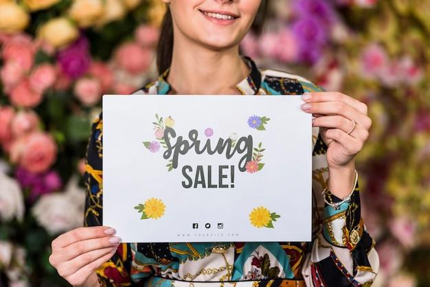 Mujer sujetando mockup de papel para rebajas de primavera