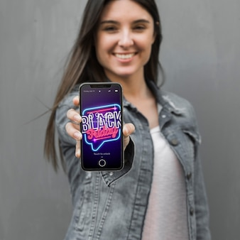 Mujer sujetando mockup de smartphone con concepto de black friday PSD gratuito
