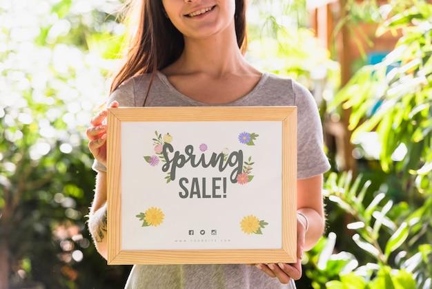 Mujer sujetando mockup de tabla para rebajas de primavera