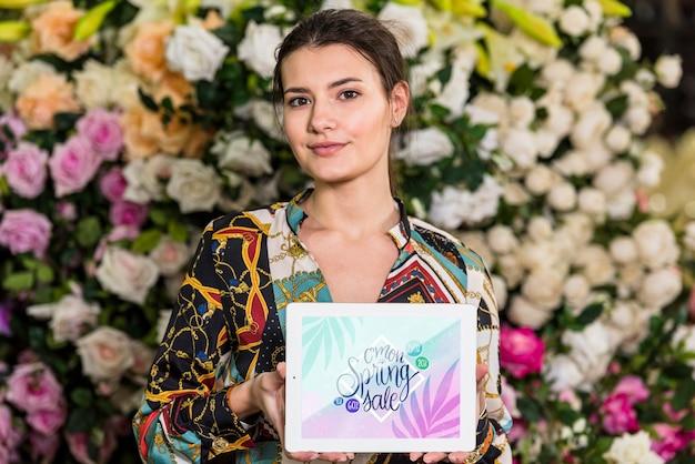 Mujer sujetando mockup de tableta para rebajas de primavera