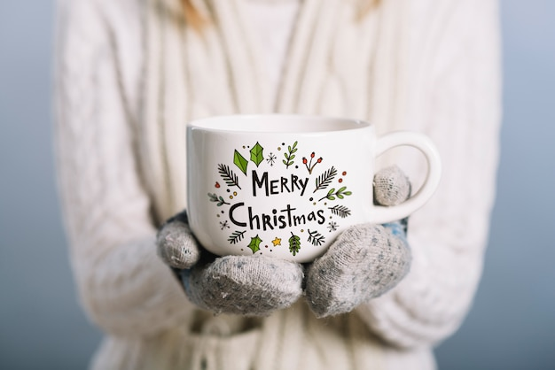 Mujer sujetando mockup de taza con concepto de navidad